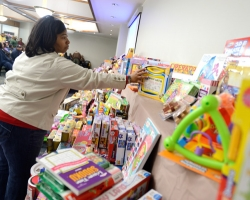 Demetria Hereford, ASsistant Director of the McNair Program, helps set out toys to be given away to university service employees at the annual Books and Bears distribution.  Photo by Nathan Latil/Ole Miss Communications