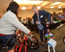 Demetria Hereford helps Tanya Gross select a bike at the annual Books and Bears distribution.  Photo by Nathan Latil/Ole Miss Communications
