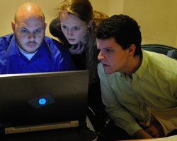 University of Mississippi students Andrew Henning (left), Kristen Vise and Mitchell Hobbs look at some of the first images rendered of the 'Archaionomia' over spring break at the Folger Shakespeare Library. UM photo by Robert Jordan.