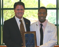 Geremy Carpenter (right), president of the UM School of Pharmacy's PY2 class, presents the Teacher of the Year award to Stephen J. Cutler, chair and professor of medicinal chemistry. Photo by Dabney Weems.