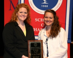 Laurie Warrington (left), clinical assistant professor of pharmacy practice at the UM School of Pharmacy,  displays the Teacher of the Year award she received from Miranda Jordan, president of the PY3 class, during the school's recent Awards Day ceremony. Photo by Dabney Weems.