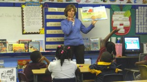 Carolyn Pegram, a volunteer and committee member at the University of Mississippi Center for Excellence in Literacy Instruction, reads 'Three Hens and a Peacock' to first-graders at Okolona Elementary School. The school is a high-needs school where CELI specialists advise K-3 teachers on literacy education.