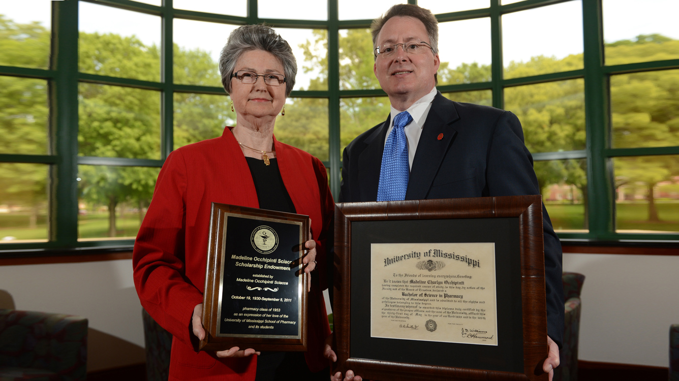 Barbara G. Wells, former dean of the University of Mississippi School of Pharmacy, and David D. Allen, the school's current dean, show off a plaque honoring Madeline O. Sciacca and Sciacca's 1953 pharmacy diploma. Both items have been hung in the pharmacy school to commemorate an estate gift of $400,000 to create the Madeline Occhipinti Sciacca Memorial Scholarship Endowment. UM photo by Kevin Bain.