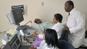 UMMC cardiology professor and Jackson Heart Study researcher Dr. Ervin Fox, standing at right, monitors as Shari Cook, foreground, and Audrey Samuels, center, take readings from JHS research participant.