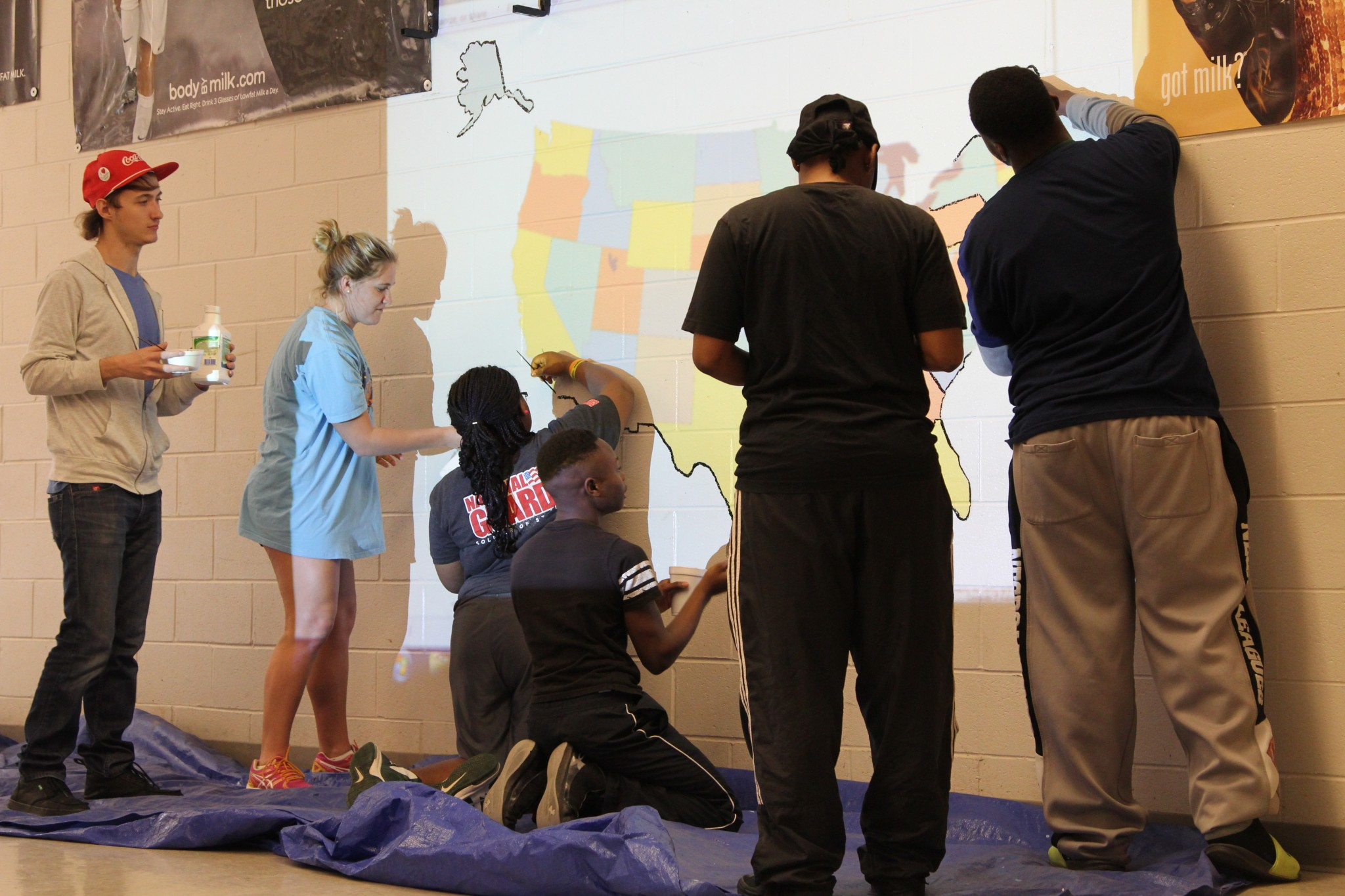 UM students work during their spring break, painting a large map on a wall at a West Tallatchie school.