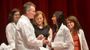 Dean David D. Allen congratulates Suman Ali on receiving her white coat at the Aug. 15 ceremony.