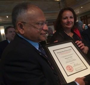 Waheed Uddin holding his award with his wife, Ruhksana