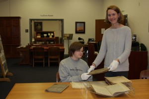 Rachel McLemore and Head of Special Collections Jennifer Ford view the recent donation of meeting minutes from the Charleston chapter of the Rotary Club.