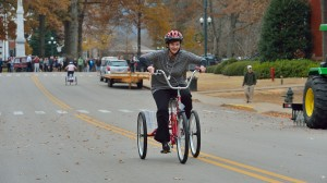 Dr. Brandi Hephner LaBanc rides a tricycle in a relay race as part of the RebelWell program.