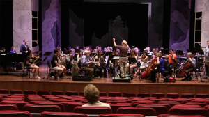 Dr. Nancy Van de Vate listens to the cast and orchestra during the Sitz Probe in the Ford Center.