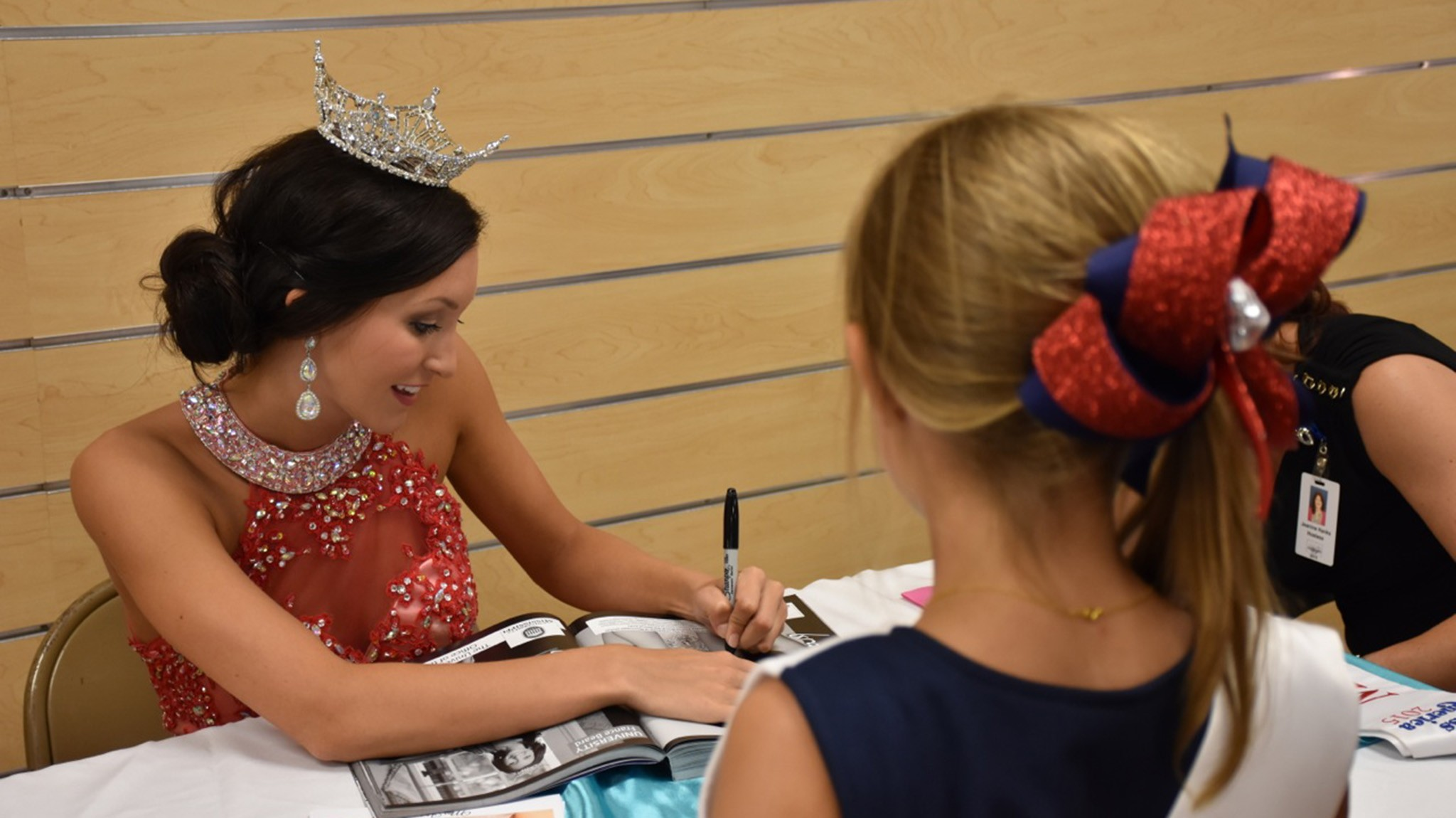 Miss University, France Beard, signs autographs for a future Rebel at an autograph party in Vicksburg. France is competing this week in Vicksburg at the Miss Mississippi Pageant.