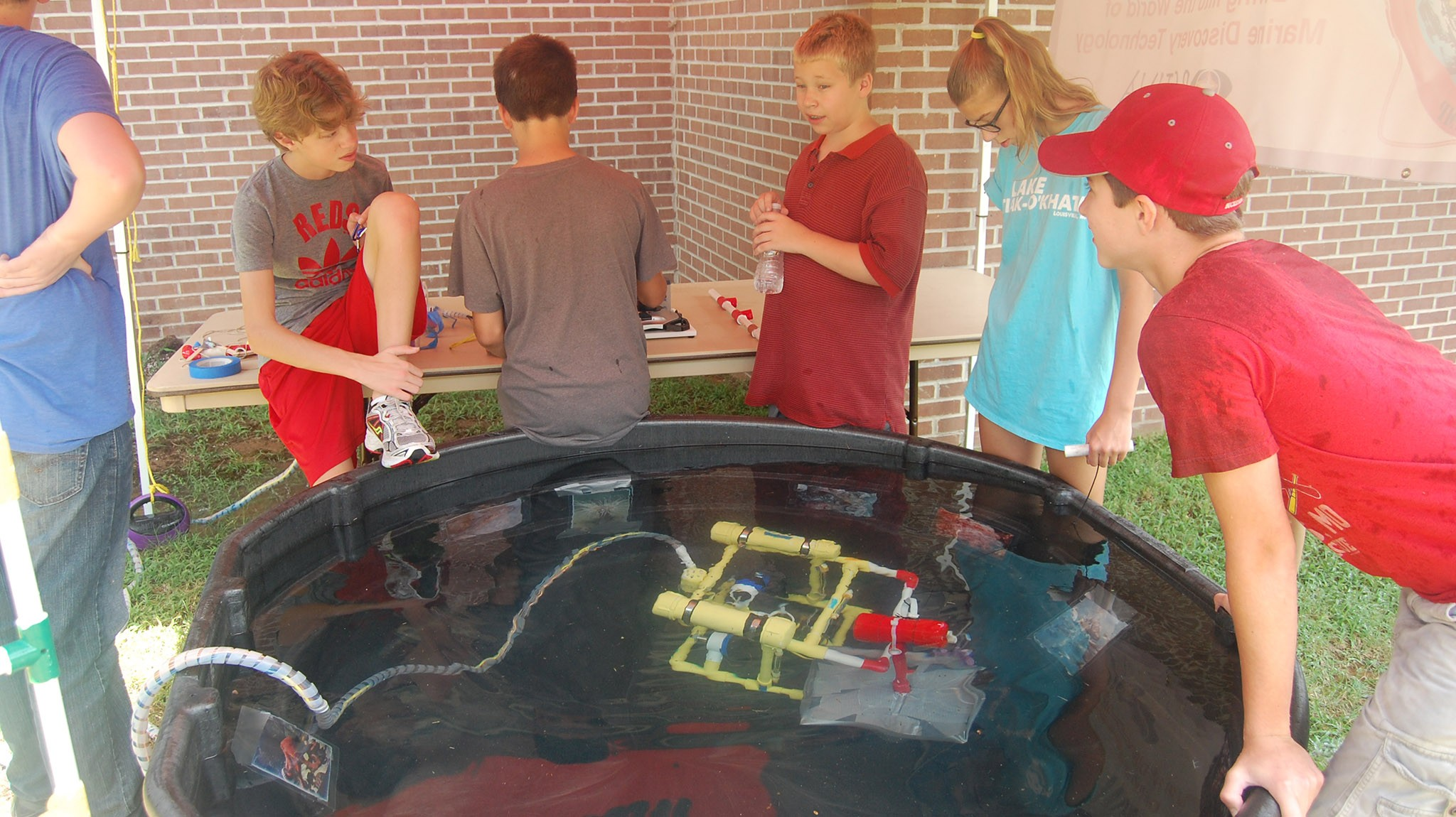 ROV Camp students watch the ROV as it moves around the tank.