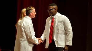 Martin Love of Brandon receives his white coat from Dean David D. Allen.