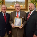 Longtime UM donor John Glass, center, holds a photo of his father, the late William Quintard Glass. John Glass is paying tribute to his father's influence with a named faculty chair in the Meek School of Journalism and New Media. On hand to thank Glass for his support are UM Foundation President/CEO Wendell Weakley, left, and School of Business Administration Development Officer Adam Lee. Part of Glass' gift also will benefit the business school. Photo by Thomas Graning/Ole Miss Communications
