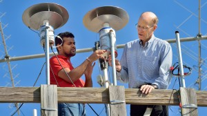UM physicists Sampath Bandara (left) and Thomas Marshall place a light sensor in place as part of their study of lightning strikes. (Photo by Robert Jordan, UM Imaging Services)
