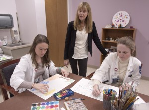 Susan Anand, center, observes as third-year medical students Lauren Williamson, left, and Caitlyn Reed, try their hand at an art therapy exercise; both are in their psychiatry rotations.