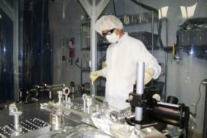 A LIGO team member inspecting the detector portion of the technology inside the laboratory.