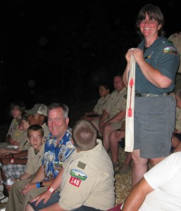 Jim Chambers is 'tapped out' into the Order of the Arrow, a Boy Scout honorary service organization, at Camp Yocona. His wife, Julie, stands behind him with an OA sash, marking him as a candidate.