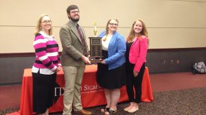UM political science professor Sue Ann Skipworth and students Connor Somgynari, Christine Sim and Katie Reid show off their Grand Champion trophy at the Pi Sigma Alpha Conference.