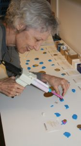 Nancy Wicker working with the polyvinyl siloxane (PVS) to make impressions from broken portions of bracteates.