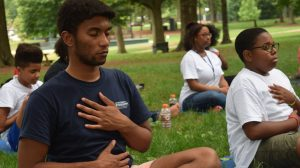 Terrius Harris and Albert Ball learn yoga in the grove.