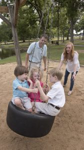 Siblings Fraiser, left, Evie Jane and Carter Johnston swing as parents Brian and Laura Beth Johnston look on. UMMC photo