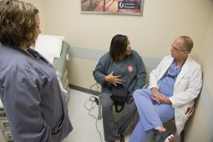 Charlotte Pegues (center) talks with registered nurse Mollie King and surgeon Dr. James Wynn during a post-op exam at the University of Mississippi Medical Center, where Pegues received a successful kidney transplant in June. Photo by Marc Rolph/UMMC Public Affairs