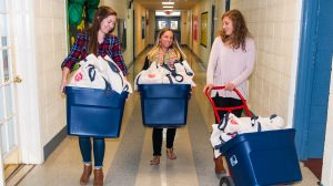UM nutrition graduate students (from left) Kelsey Reece, Michelle Weber and Sydney Antolini deliver bags of vegetables to classrooms at Bruce Elementary School, where they will be distributed to children as part of the university's six-week Farm to YOUth project. Photo by Bil Dabney