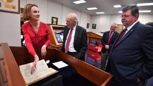 Jennifer Ford shows Shakespeare's Second Folio to Jesse L. White, Associate Provost Noel Wilkin and Provost Morris Stocks. Photo by Kevin Bain/Ole Miss Communications